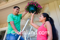Pic of a hispanic couple at home on the patio hanging a basket of flowers up on their new home. They are happy and smiling as they do their home improvement projects together.